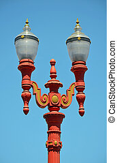 Red ornamental lightpost against blue sky