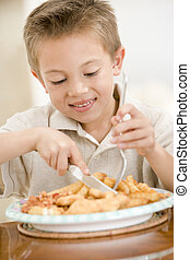 Young boy indoors eating fish and chips smiling