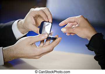 marriage proposal - close up of young couple getting...