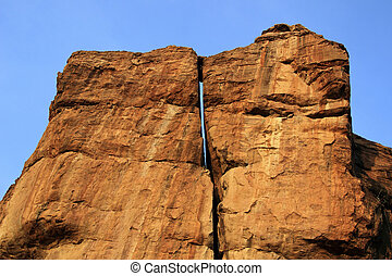 Sunlit Rocky Twins - Huge rock surfaces soaked in morning...
