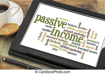 passive income word cloud on a digital tablet with a cup of...
