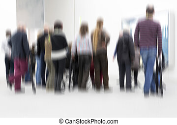 Group of people inside an exhibition hall, blurry