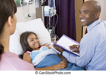 Doctor Making Notes On Young Girl