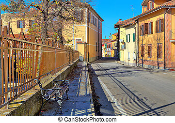 Bench on sidewalk and road through town in Italy - Bench on...