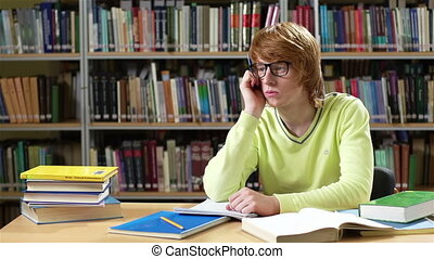 Geeky student with a pensive look studying for exams in the...