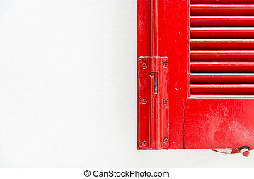 Edge of red wooden window with white wall