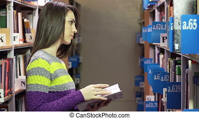 Between Shelves - Serious girl standing between library...