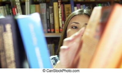Library Archive - University girl choosing a book in the...