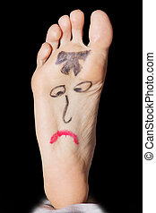 Painted sad face on the woman's feet on a dark background.