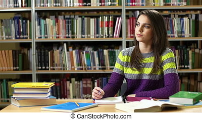 Library Homework - Lovely female student doing her homework...