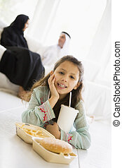 Young girl with fast food in living room smiling with...