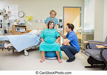 Birthing Mother Having Contraction - Mature nurse and man...
