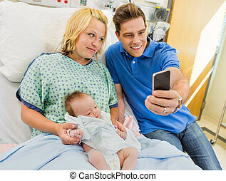 Mid adult man with woman and newborn babygirl taking...