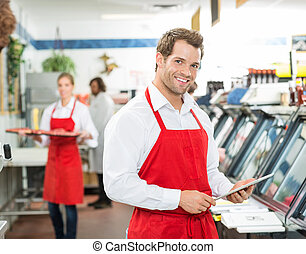 Portrait Of Happy Butcher Holding Digital Tablet At Store -...