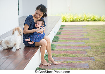 Mom and Baby are watching a puppy on wooden balcony - Mom...