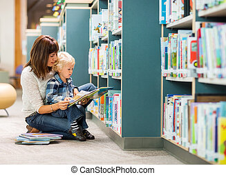 Student With Teacher Reading Book In Library - Elementary...