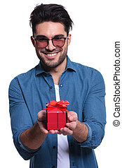 smiling young man is offering a red gift box
