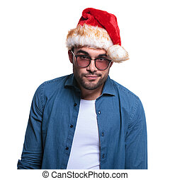 undecided young man in santa hat