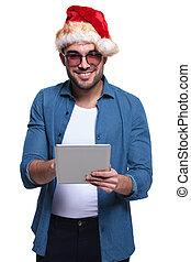 young man wearing santa hat is working on a tablet
