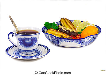 A Cup of tea and a bowl filled with cakes, sweets, fruits....