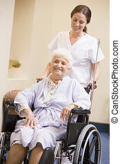 Nurse Pushing Senior Woman In Wheelchair