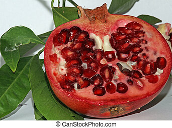 Pomegranate red ripe with beans very juicy and leaves -...