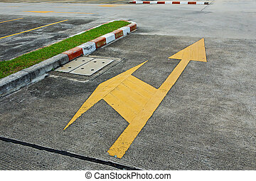 A yellow traffic arrow signage on an asphalt road indicating...