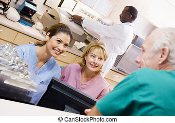 Nurses Talking At The Reception Area In A Hospital