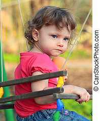 Cute child girl swinging and looking serious on summer...