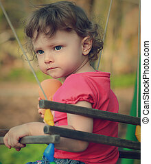 Serious cute baby thinking on swing Closeup portrait