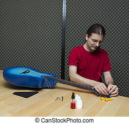Replacement of guitar strings - Guitar technician replacing...