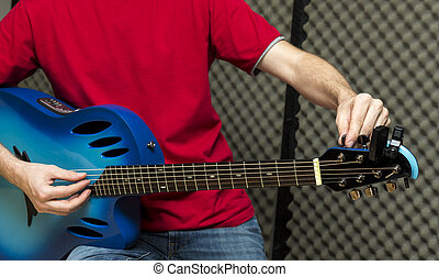 Tuning the guitar - Guitarist tuning his guitar Series with...