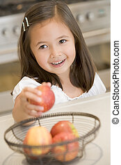 Young girl in kitchen getting apple off counter smiling