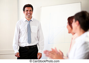 Adult businessman looking at female coworker