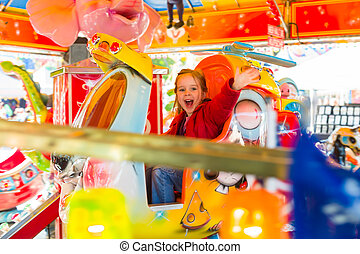 child rides on kirtag in ringelspöiel - a little girl has...