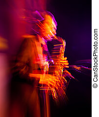 Saxophone player performing on stage. Intentional motion...