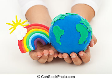 Ecology concept - a clean earth in child hands with colorful...