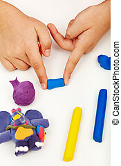 Child hands with colorful clay - Child hands playing with...