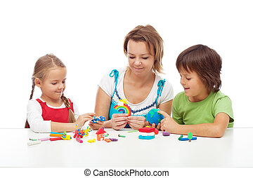 Woman and kids playing with colorful clay molding different...
