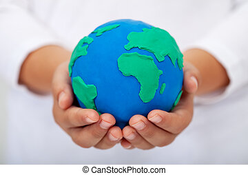 Our home - child holding earth made of clay - Our home -...