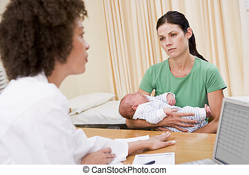 Doctor with laptop and woman in doctors office holding baby...