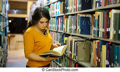 Girl studying in library - Happy young female student...