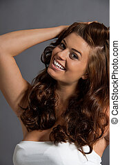 smiling attractive young woman with long wavy dark hair...