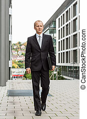 smiling successful business man in black suit outdoor