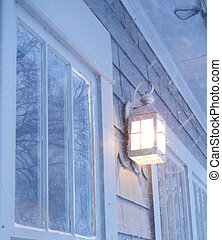 Light glowing in snowstorm - Outdoor light glowing against...