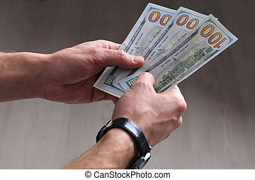 hundred dollar banknotes in man's hands