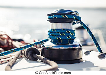 Closeup on yacht cord crank, rope holder on white sail...