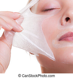 Portrait blond girl in facial mask. Part face. Beauty and...