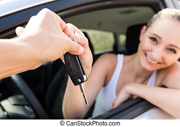 young smiling woman sitting in car taking key handover rent...