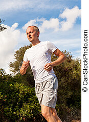 athletic man runner jogging in nature outdoor fitness summer...